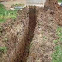 Выкопанная траншея под газопровод от газгольдера к дому